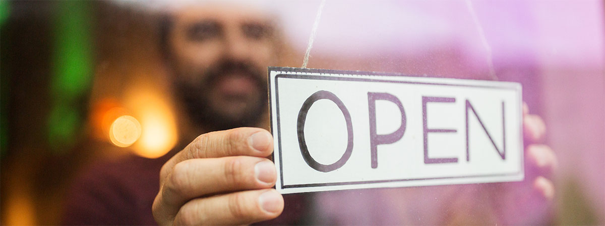 a man putting an open sign in his business window