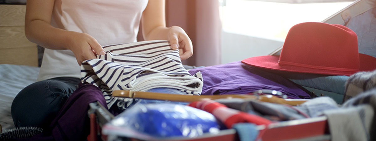 a woman packing clothing into her suitcase