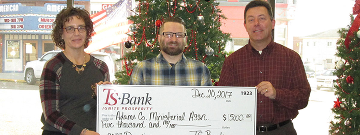 ts bank employees deliver check to adams county ministe
