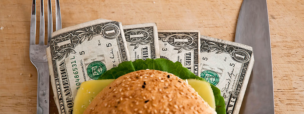 hamburger sitting on dollar bills with fork and knife