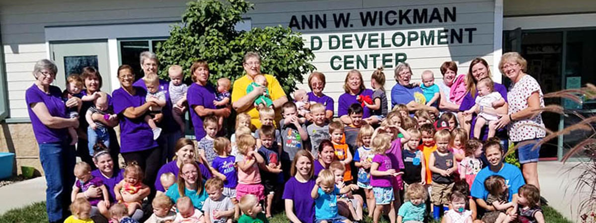 children and staff standing outside of the ann wickman