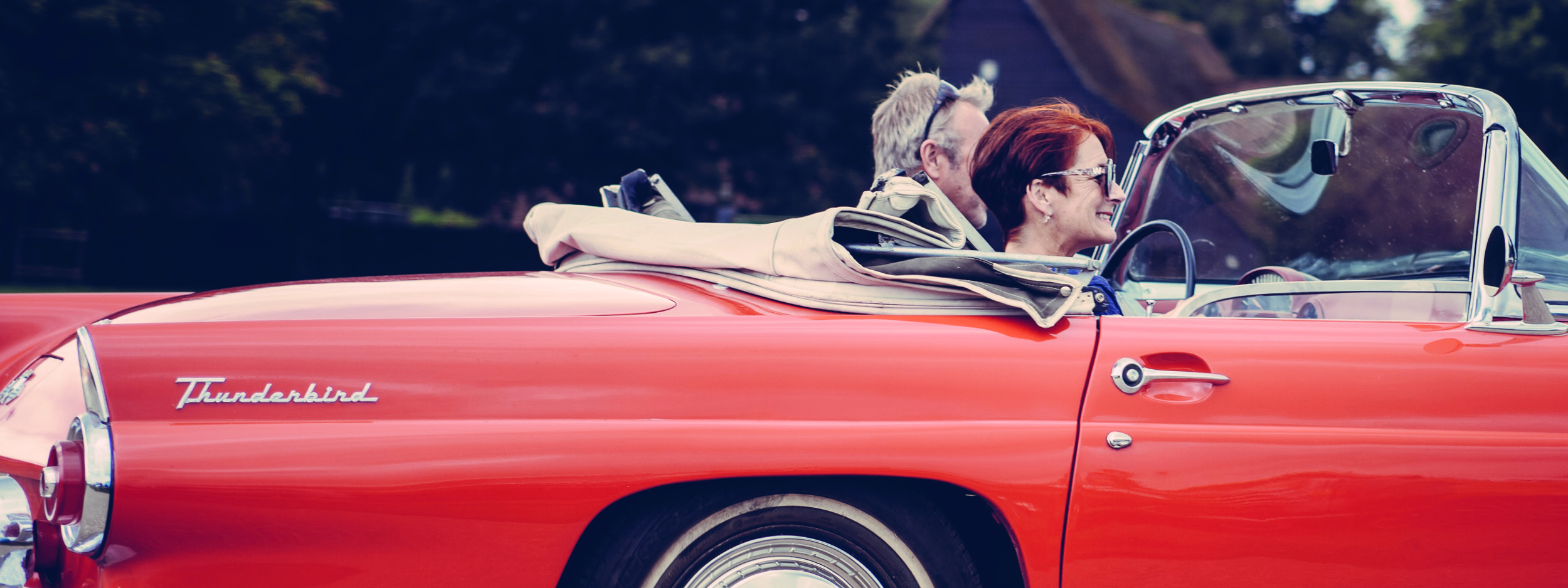 a middle aged couple riding in a convertible
