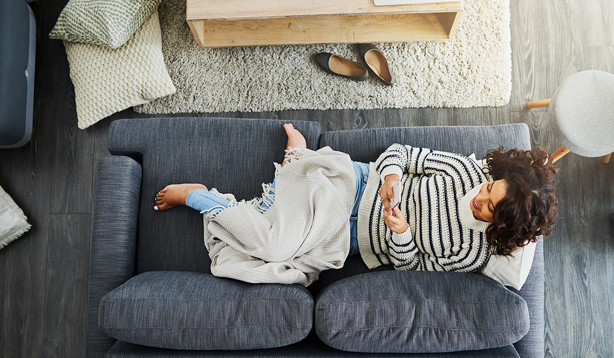 woman lying on the couch on her phone